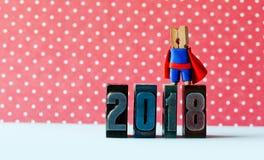 Toppet lyckat kort för nytt år 2018 Modig superheroledare som poserar på tappningboktrycksiffror Härlig klädnypa Royaltyfria Foton