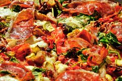 Toppings pizza with prosciutto, vegetables Stock Photo