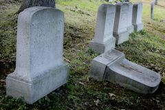 Grave Marker at an Old Cemetery. A toppled headstones lies next to upright ones in the late afternoon an old Cemetery in Rochester, New York, July 2018 Stock Photography
