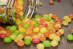 Toppled over glass jar full of colorful sweets Stock Photos