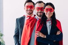 toppna businesspeople i maskeringar och uddar som ser kameran fotografering för bildbyråer