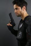 Toppna snutar - stilig man som poserar med ett vapen arkivfoto