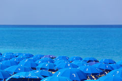 Tops of blue parasols and sea Stock Image