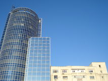 Tops of contrasting buildings on blue sky Stock Images