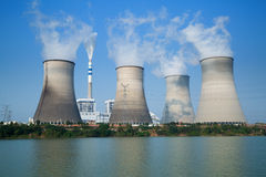 Tops de torres de enfriamiento de la central nuclear debajo del cielo azul Foto de archivo
