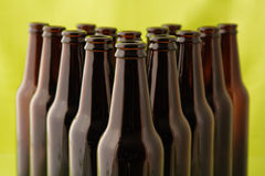 Tops of empty beer bottles in front of green Stock Images