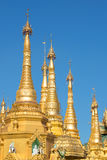 The tops of the golden stupas of the Shwedagon pagoda against the blue sky. Yangon, Myanmar Royalty Free Stock Photography