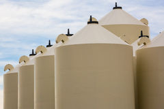 Tops of grain bins in a diagonal alignment Stock Photo