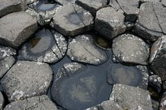 Tops of grey basaltic prisms with water in Ireland stock photo