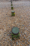 Tops of Groynes, part buried by pebbles. Stock Images