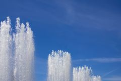 Tops of large fountain jets gushing upwards against blue sky. May be used as background stock images