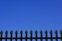 Tops of metal palisade fencing. Against a blue sky with space for text royalty free stock images