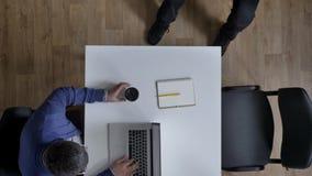 Topshot av affärsfolk som arbetar i det moderna kontoret, kameraflyttning ovanför affärsmän som sitter på tabellen som koncentrer stock video