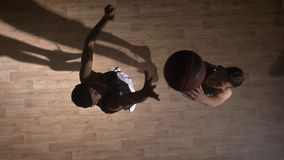 Topshot, two opposing basketball players facing each other on court, trying to take ball