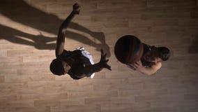 Topshot, zwei gegenüberliegende Basketball-Spieler, die auf dem Gericht, versuchend, Ball zu nehmen sich gegenüberstellen