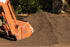 Topsoil. Front end loader scooping up some rich garden compost topsoil Stock Photography