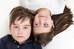 Topsy turvy children. Overhead shot of two children laying on the floor looking up Stock Image