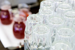Topsy-turvy glasses on counter with gugs of red drink. Upside-down glasses on counter with gugs of red drink Stock Image