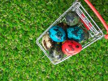 Topview五颜六色在红色购物车的多复活节彩蛋在绿草 免版税库存照片