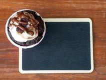 Topview av chokladmuffin och chokladkaramell överträffar, och svart tavla är en bakgrund på trätabellen Royaltyfria Foton
