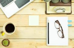 Topview av trätabellen med den kontorshjälpmedel och växten Royaltyfri Fotografi