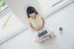 Topview del blogger alegre, mecanografiando en el ordenador portátil en casa que se sienta encendido Fotografía de archivo