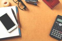Topview des hölzernen Desktops mit Bürowerkzeugen Spott oben, Weichzeichnung Lizenzfreie Stockfotos