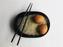 Topview-Isolatessstäbchen, Reis, Ei in der Schüssel in Asien-Art lizenzfreie stockfotografie