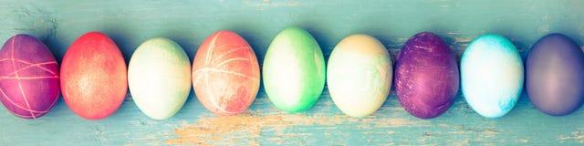 Topview, ovos da páscoa tingidos coloridos na tabela de madeira do vintage azul Foto de Stock