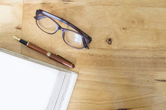topview of wooden working desktop in office. Glasses, pen and empty white book page. Royalty Free Stock Images