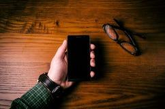 Toque da mão do homem em uma tela do telefone celular em uma tabela de madeira Situação de negócio fotografia de stock
