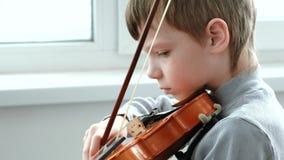 Toque el violín Siete años del muchacho que toca el violín cerca de una ventana almacen de metraje de vídeo
