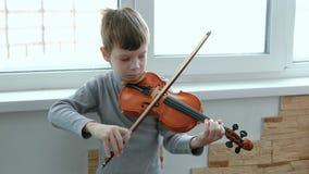 Toque el violín Siete años del muchacho que toca el violín cerca de una ventana Front View almacen de metraje de vídeo