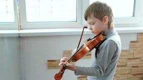 Toque el violín Siete años del muchacho que toca el violín cerca de una ventana Vista lateral almacen de metraje de vídeo