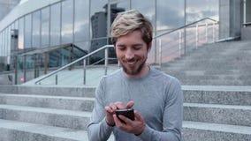 Toque feliz do homem um smartphone vídeos de arquivo