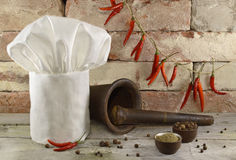 Toque with kitchen ware and peppers Stock Photos