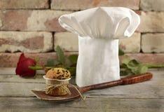 Toque mit Muffin und Rotrose lizenzfreie stockfotos