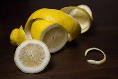 Torção da casca de limão ou do limão em um fundo de madeira do marrom escuro As fatias do limão são cortadas transversalmente Fim imagens de stock royalty free