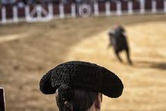 Toréador espagnol donnant sur le taureau pendant une corrida tenue Images stock