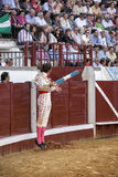 Toréador espagnol Juan Jose Padilla sautant et suspendu dans le ciel avec deux banderillas dans la main droite regardant le taurea Image stock