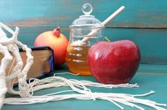 Torah book tallit pomganet honey and apple background. Torah book, tallit, pomganet, honey jar and red apple on a turquoise background. Rosh Hashanah Jewish new Royalty Free Stock Photography