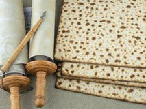 A fragment of the Torah scrolls on parchment, a pointer and a matzoh baked in the oven royalty free stock photos
