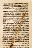 Torah and Yad Pointer. Torah scroll opened to Deuteronomy 6:4, known as the Shema, with a gold yad pointing to the place stock photos