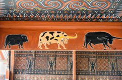 Toraja traditional house wood carvings and paitings with different buffaloes and pig royalty free stock photography