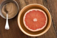 Toranja cor-de-rosa partida ao meio fresca servida com açúcar Fotografia de Stock Royalty Free