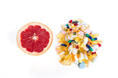 Toranja e comprimidos, suplementos à vitamina no fundo branco com espaço da cópia, conceito da dieta saudável Fotos de Stock Royalty Free