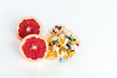 Toranja e comprimidos, suplementos à vitamina no fundo branco, conceito da dieta saudável Imagens de Stock Royalty Free