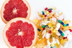 Toranja e comprimidos, suplementos à vitamina no fundo branco, conceito da dieta saudável Imagem de Stock Royalty Free