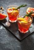 A toranja e os alecrins descaroçam o cocktail, refrescando a bebida com gelo imagens de stock