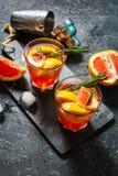 A toranja e os alecrins descaroçam o cocktail, refrescando a bebida com gelo imagens de stock royalty free